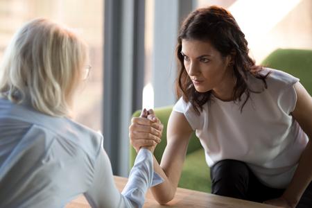 Vista laterale della decisiva donna d'affari millenaria concentrata braccio di ferro con la lotta concorrente femminile per la leadership, le lavoratrici in lotta di confronto o in competizione. Concetto di rivalità