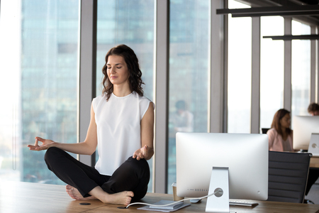Peaceful millennial businesswoman sit at office table practicing yoga in lotus position, calm female employee meditating in coworking space, breathing deep clearing mind. Stress free concept