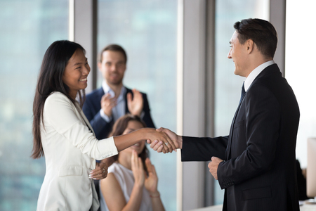 Male company CEO shake hand of shy female Asian employee congratulating with job promotion, middle-aged businessman handshake woman worker at meeting greeting with employment. Reward concept