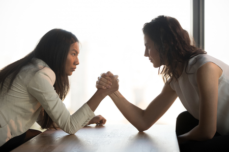 Two multiracial millennial women sit opposite look in eyes arm wrestle to get leadership at work, strong decisive female fight compete with rival, show authority. Confrontation, rivalry concept