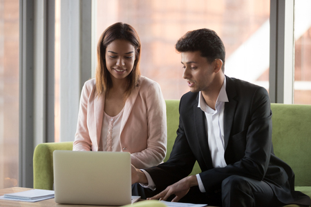 Smiling multiracial millennial businesspeople discuss collaboration sit at office table using laptop, businessman negotiate with female business client near computer at briefing. Partnership concept