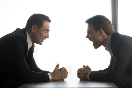 Uomini d'affari pazzi si siedono al tavolo uno di fronte all'altro con le mani serrate litigano urlando al concorrente, rivali di uomini millenari arrabbiati in confronto urlano dibattito sulla scrivania, negoziano ad alta voce. Concetto di rivalità Archivio Fotografico