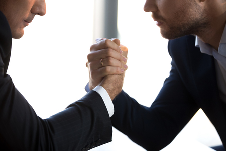 Close up of serious businessmen sit at table arm wrestling at workplace competing for leadership, focused men competitors fight to gain power or authority, win struggle. Rivalry, confrontation concept