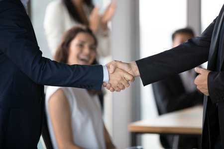 Close up of businessmen shake hand closing deal after successful negotiations in office, business partners handshake greeting signing agreement after discussion or get acquainted. Partnership concept