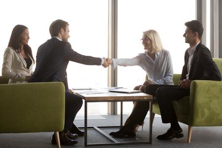 L'uomo d'affari millenario stringe la mano del partner commerciale maturo che saluta al briefing casuale, stringe la mano dei soci chiudendo l'accordo o prendendo un accordo dopo una negoziazione riuscita. Concetto di partenariato Archivio Fotografico