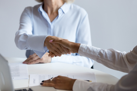 Close up African American businesswoman shaking hand of mature employee, business partners sitting at table at negotiations in boardroom, greeting or getting acquainted at company meeting