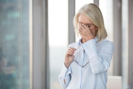 Mujer madura cansada quitarse las gafas masajeando los ojos que sufren de dolor de cabeza severo, mujer de mediana edad agotada que tiene problemas de visión o visión borrosa, sintiéndose mal trabajando demasiado tiempo en gafas