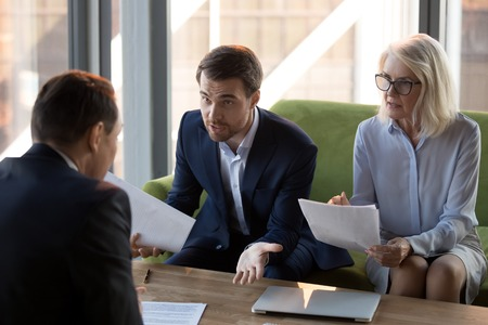 Concerned businesspeople argue with colleague or client dissatisfied with contract terms, mad worried businessman have dispute with business partner unhappy with agreement, claiming money back Foto de archivo