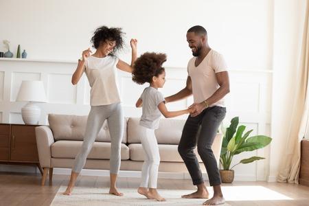 Fröhliche lustige aktive afrikanische Familie mit süßer kleiner Tochter, die zu Hause tanzt, unbeschwerte, fröhliche schwarze Eltern, Mama, Papa und kleines Mädchen, das Spaß beim Springen und Lachen hat