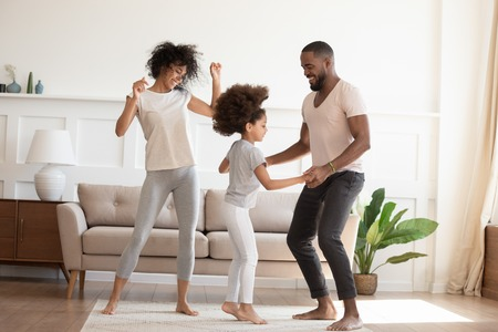 Happy funny active african family with cute little kid daughter dancing at home, carefree cheerful black parents mom dad and small child girl having fun jumping laughing enjoy leisure in the morning 스톡 콘텐츠 - 124264237