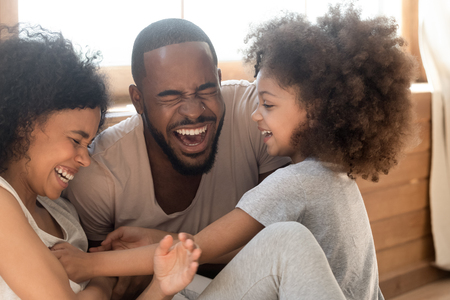 Happy african american family with cute little kid daughter tickling laughing at home together, cheerful black parents and small child girl having fun playing bonding enjoy funny lifestyle activity