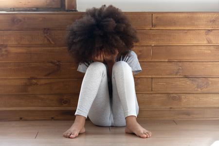 Triste stressata piccola ragazza afroamericana che piange, sconvolto bambino solitario vittima di bullismo si sente abbandonato abusato, bambino orfano nero in età prescolare in lacrime seduto da solo sul pavimento, abuso di bambini, concetto di infanzia infelice