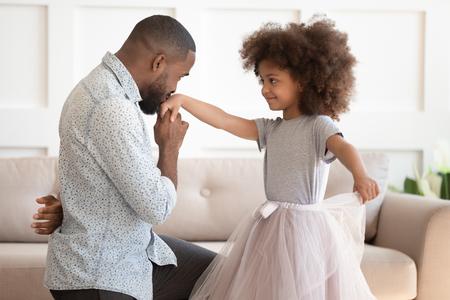 Liebevoller junger afroamerikanischer Vater, der auf Knien steht und sich bei der süßen kleinen Tochter für den Tanz bedankt, glücklicher schwarzer Vater spielt mit der kleinen Mädchenprinzessin, die küssende Hand hält und zusammen Spaß zu Hause hat