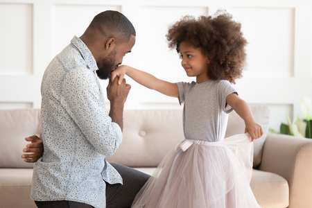 Loving young african american dad standing on knee thanking cute little child daughter for dance, happy black father play with small kid girl princess holding kissing hand having fun at home together