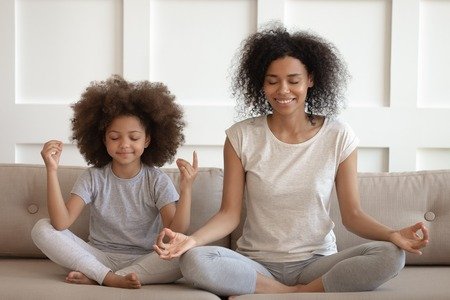 Healthy calm african american mother teaching meditation sit with cute small child daughter on sofa, mindful happy black mom and kid girl doing yoga exercises relaxing together in lotus pose at home
