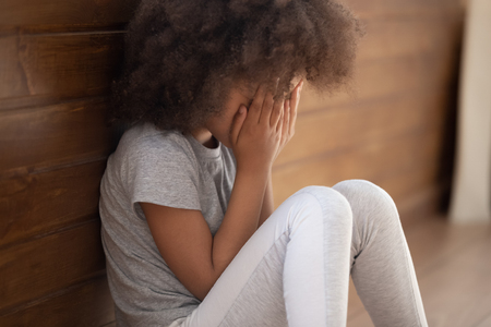 Verärgertes kleines afroamerikanisches Kindermädchen, das das Gesicht mit den Händen bedeckt, das allein auf dem Boden sitzt, trauriges einsames Waisenkind, das gemobbt wird, missbraucht, sich gestresst oder verängstigt fühlt, Konzept des Gewaltmissbrauchs von Kindern Standard-Bild