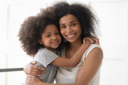 Schöne afroamerikanische Familie, junge alleinerziehende Mutter und süße kleine Tochter umarmen das Bonding mit Blick auf die Kamera, sitzen zusammen auf dem Bett, glückliche schwarze Mutter mit kleinem Mädchen umarmt sich im Schlafzimmerporträt
