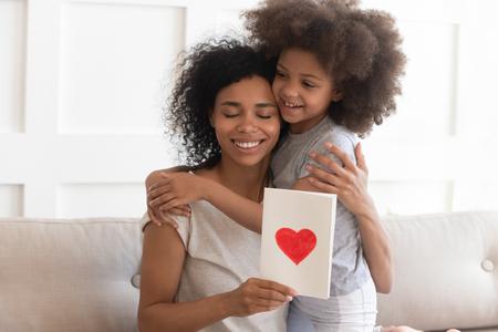 Feliz joven madre soltera afroamericana abrazando a la pequeña hija linda agradeciendo por el regalo, sonriendo a mamá negra abrazando a un niño pequeño sosteniendo una tarjeta de felicitación con un corazón rojo que se une en el concepto del día de la madre
