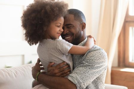 Zoete momenten van vaderschap concept, gelukkige Afrikaanse vader houden omhelzing schattig klein kind dochter, glimlachend zwarte familie gemengd ras papa en klein kind knuffelen knuffelen genieten van tijd samen thuis