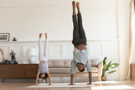 Cute active african kid girl copy imitate father doing gymnastic handstand exercise in living room, sporty family black dad and child daughter stand on hands upside down having fun together at home Banco de Imagens