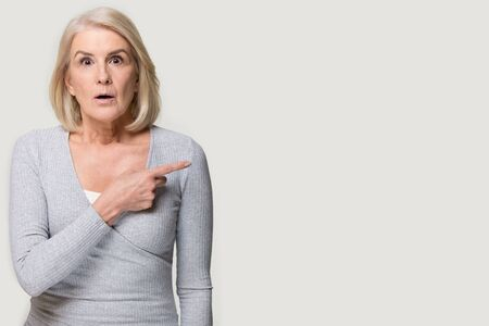 Middle aged senior blond woman looking at camera isolated on grey studio background feels astonished stunned pointing finger at copy space announcement advertisement text, shocking news offer concept