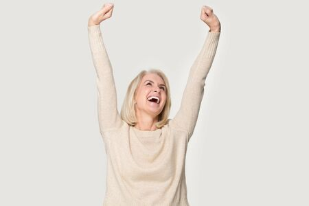 Excited senior woman raised stretched hands open mouth laughing screaming with joy feels happy isolated on grey studio background, weekend no stress euphoric lucky lady celebrating lottery win concept Stock Photo
