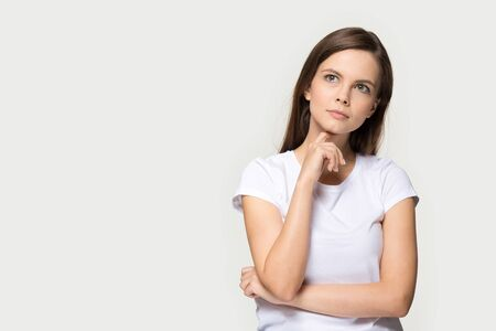 Pensive focused millennial caucasian woman wearing white t-shirt touch chin thinking stands aside isolated on grey studio background copy space for text advertisement or wise thoughts concept image. Banco de Imagens