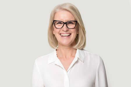 Head shot portrait laughing old businesswoman in glasses white blouse looks at camera feels happy pose isolated on grey studio background, experienced professional business coach teacher concept image Standard-Bild