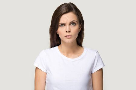 Head shot portrait sceptic suspicious woman wearing white t-shirt frown eyebrows feels dissatisfied isolated on studio grey background, confused grumpy girl negative emotions irritated person concept Foto de archivo - 124554791