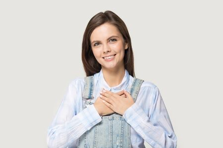 Attractive girl in jean coverall on grey studio background smile looks at camera holds hands on chest feels gratitude benevolence, gesture of sincere feelings from heart and love support care concept
