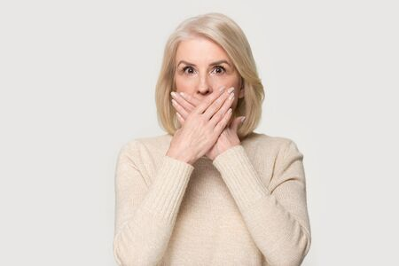 Scared middle aged senior woman looks at camera makes big eyes covering mouth with hands feel horrified, stunned old blond female received shocking news posing isolated on white grey studio background