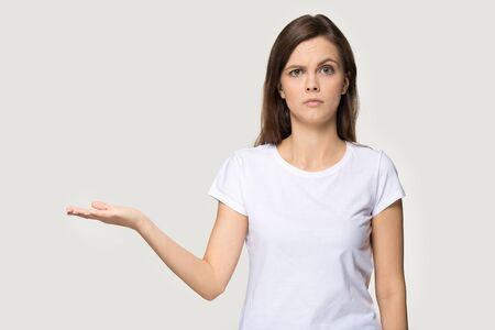 Dissatisfied millennial woman in white t-shirt looking at camera showing empty open palm copy space isolated on grey studio background, frowning girl grumpy face expression feels skeptic concept image