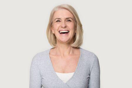 Colpo di testa ritratto felicissimo bionda femmina di mezza età sorridente guardare la telecamera ridendo si sente felice posa isolata su sfondo grigio studio, pubblicizzare la procedura clinica protesi per cure odontoiatriche per gli anziani