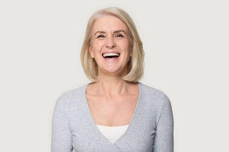 Head shot portrait overjoyed blond middle aged female smiling look at camera laughing feels happy pose isolated on grey studio background, advertise clinic procedure dental care prosthesis for seniors 写真素材 - 124554827