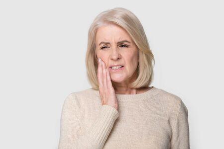Colpo alla testa ritratto in studio senior femmina bionda posa su sfondo bianco grigio, tocca la guancia che soffre di improvviso dolore ai denti si sente malsano infelice bisogno di aiuto per il servizio dentistico, concetto di assicurazione medica