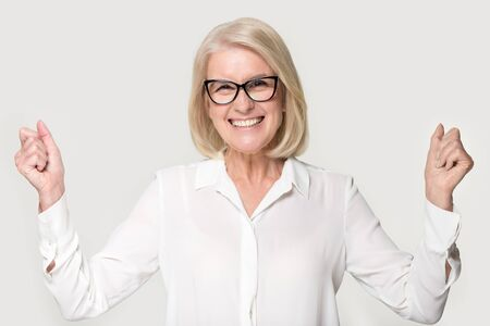 Head shot portrait excited middle aged entrepreneur businesswoman in glasses on grey background, senior female look at camera feels overjoyed rejoice succeed reached goal celebrate victory win concept