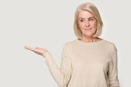 Middle aged positive blonde woman showing holding open palm offering new medical beauty procedure anti-aging product posing isolated on grey studio background copy space for advertisement text concept.