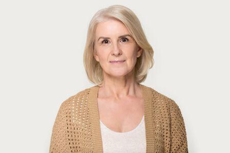 Kopfschussporträt attraktive reife fünfzigjährige Frau mit brauner Strickjacke Pose auf grauem Studiohintergrund, gesunde pensionierte weibliche natürliche Schönheit, Gesundheitswesen, Krankenversicherungskonzeptbild