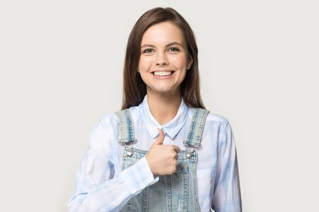 Pretty woman smiling looking at camera showing thumbs up pose studio grey background give best recommendations dental clinic procedure, teeth whitening dentistry industry advertisement concept image