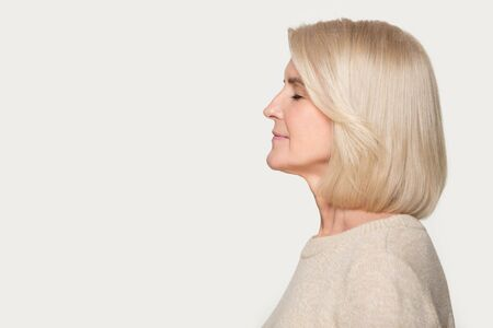 Side view old blond woman standing on grey background aside empty copy space for advertisement text, senior lady profile face closed eyes enjoy fresh air nice fragrance smell aroma or dreaming concept