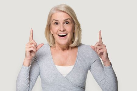 Head shot portrait on grey background mature woman gesturing points fingers up advertise product services feels excited, having good idea reach inspiration motivation or found solution eureka concept