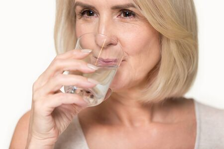 Close up studio image attractive healthy aged woman holding glass drinking enough still water, prevention dehydration in older adults, healthy habit lifestyle, helps digestion, health benefits concept Stock Photo
