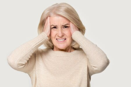 Mature woman looks at camera holding head in hands feels unhealthy studio shot on grey background, stressed female suffers from headache or migraine, senior mental disorder and dementia concept image 写真素材