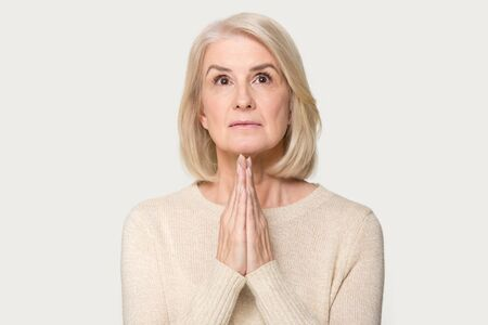 Head shot studio portrait on grey background middle aged senior woman holds hands together praying looking up having sincere request ask please heart filled with faith belief, wait for miracle concept Stock Photo