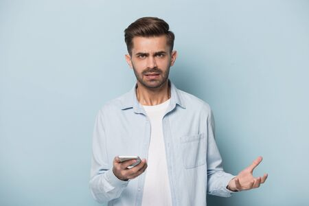Isolated on blue background angry annoyed man frowns look at camera holding smart phone having problems with wi-fi no wireless connection, need repair broken phone, unpleasant message received concept Stock Photo