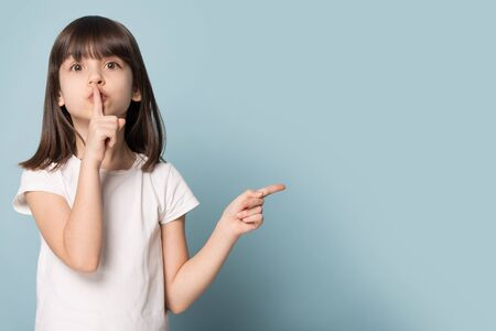 Adorable six years old little girl holding finger on lips symbol of hush gesture of asking to be quiet. Silence or secret concept image isolated on blue studio background with copy free space for text 免版税图像