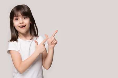 Six years old brown-haired little girl isolated on grey beige background, european appearance kid feel wondered look at camera pointing fingers aside at copy space freespace for your ad text concept