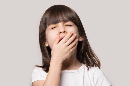 Niña de pelo castaño que se siente cansada o con sueño tapa la boca con los ojos cerrados de la mano bostezando aislado sobre fondo beige de estudio, cara de cerca el niño preescolar adorable sufre de aburrimiento