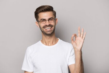 Happy guy showing ok sign look at camera isolated on grey background, man wearing glasses feels satisfied, client advise advertise eyewear store or services, everything goes according to plan concept