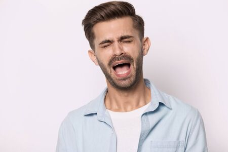 Head shot portrait of hysterical face expressions guy closed eyes screaming or whines isolated on grey white studio background, nagging man feeling desperate, singer singing song expressively concept Stockfoto